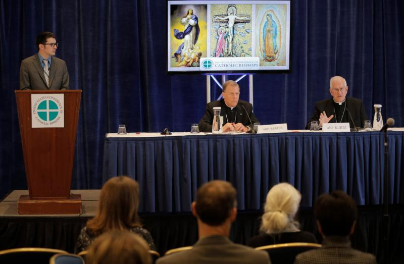 Archbishop Joseph E. Kurtz of Louisville, Ky., president of the U.S. Conference of Catholic Bishops, right, responds to a reporter's question Nov. 16 during a news conference at the bishops 2015 fall general assembly in Baltimore. At left is Don Clemmer, USCCB assistant director of media relations, and Archbishop John C. Wester of Santa Fe, N.M. (CNS photo/Bob Roller)