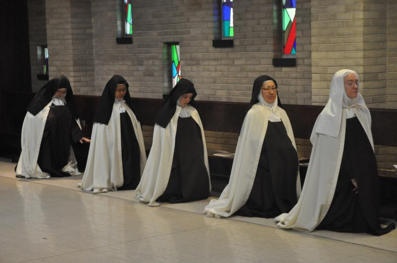 Discalced Carmelite Sisters Mary Grace Melchior, Marianna So, Marie Cecile Franer, Susanna Choi and Christine Rosencrans kneel in prayer at the Carmelite Monastery of St. Joseph in Terre Haute, Ind., during an Oct. 10 Mass to celebrate the 500th anniversary of the birth of St. Teresa of Avila, foundress of their order. (CNS photo/Sean Gallagher, The Criterion)