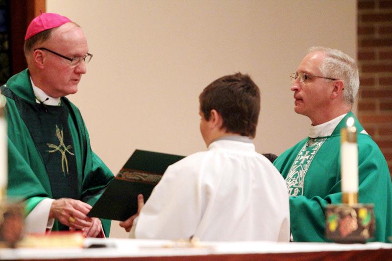 Bishop Michael Fitzgerald installs Fr Davis as the new pastor of Assumption B.V.M. Church