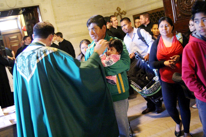 Father Thomas Viviano blesses families attending Hispanic Family Day at St. Charles Seminary Nov. 8. (Sarah Webb)