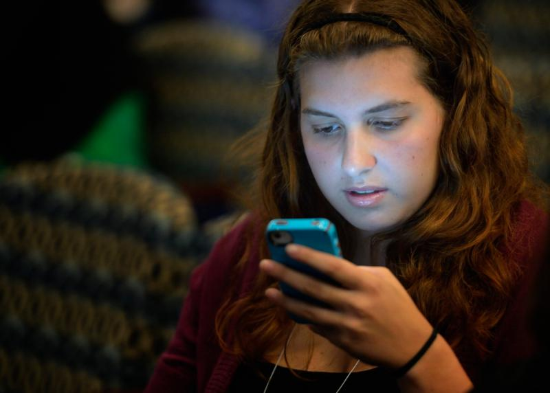 A young woman tweets a message during a 2012 conference in Washington. A new study on media usage by children ages 8-18 shows that teenagers ages 13-18 use media an average of nearly nine hours a day. (CNS photo/Paul Jeffrey)