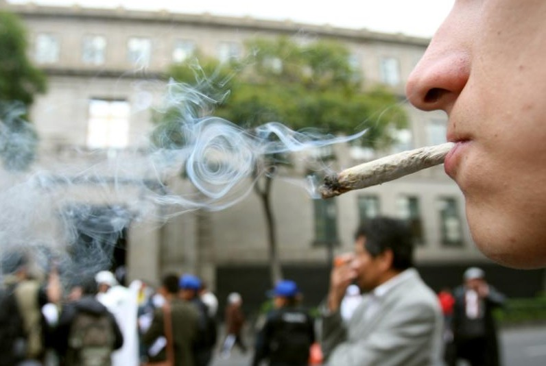 A man smokes pot during a demonstration in front of the Supreme Court in Mexico City Oct. 28. Catholic officials have condemned a Mexican Supreme Court ruling on recreational marijuana use, which they say could put the country on the path to legalization. (CNS photo/Mario Guzman, EPA)