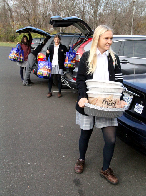 Students from Pope John Paul II High School deliver food bought with money they collected for those in need Nov. 24 at Catholic Social Services' Montgomery County Family Service Center in Norristown. (Sarah Webb)