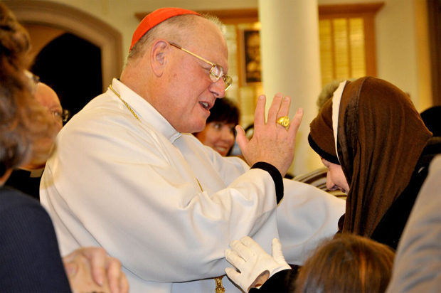 The cardinal blesses a religious sister after the Mass.