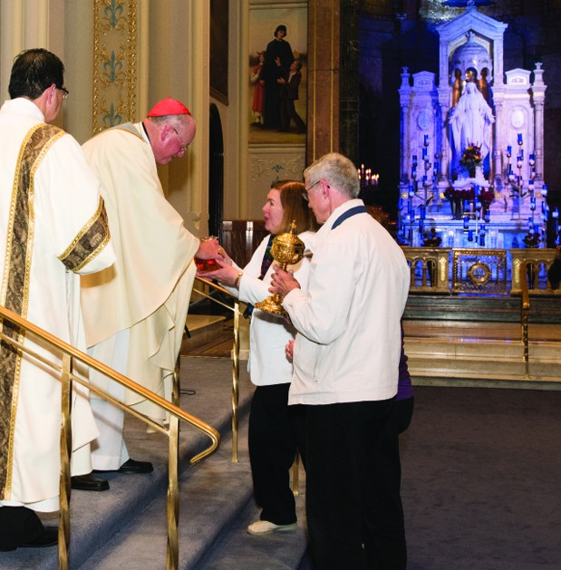 Cardinal Timothy Dolan of New York accepts the offertory gifts during Mass at the Solemn Novena at the Miraculous Medal Shrine, shown at right, which is celebrating its 100th year in Germantown. (Anne Pryce)