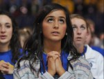 Alaina Sincich, a member of St. John Neumann Parish in Sunbury, Ohio, kneels in prayer Nov. 21 during the closing Mass of the National Catholic Youth Conference at Lucas Oil Stadium in Indianapolis. The Mass was attended by 23,000 youths from across the country. (CNS photo/Sean Gallagher, The Criterion)