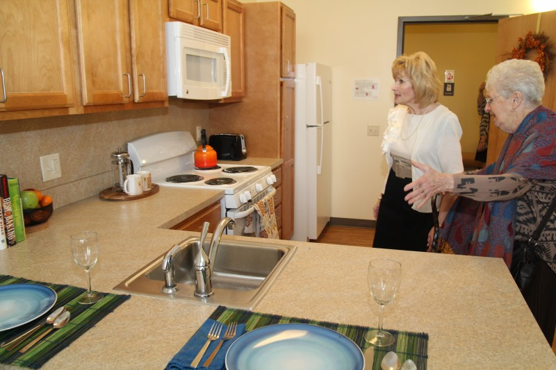 A prospective resident examines one of the efficiency apartments, rent-controlled to allow seniors to age in their neighborhood in comfort and security. (Sarah Webb)