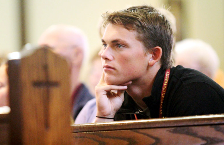 Kody Cracknell listens as Bishop Fitzgerald delivers his homily.