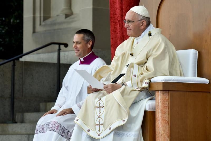 Msgr. John Cihak, a priest of the Archdiocese of Portland, Ore., sits with Pope Francis Sept. 23 during St. Junipero Serra canonization Mass in Washington. Msgr. Cihak, who grew up near Corvallis, Ore., is a papal master of ceremonies and a staffer at the Vatican's Congregation for Bishops. (CNS photo/Matthew Barrick)