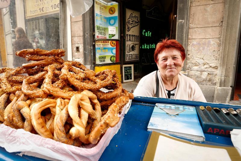 "A woman sells ""obwarzanek krakowski,"" the bagel of Poland, in early September on a street in Krakow, Poland. (CNS photo/Nancy Wiechec)"