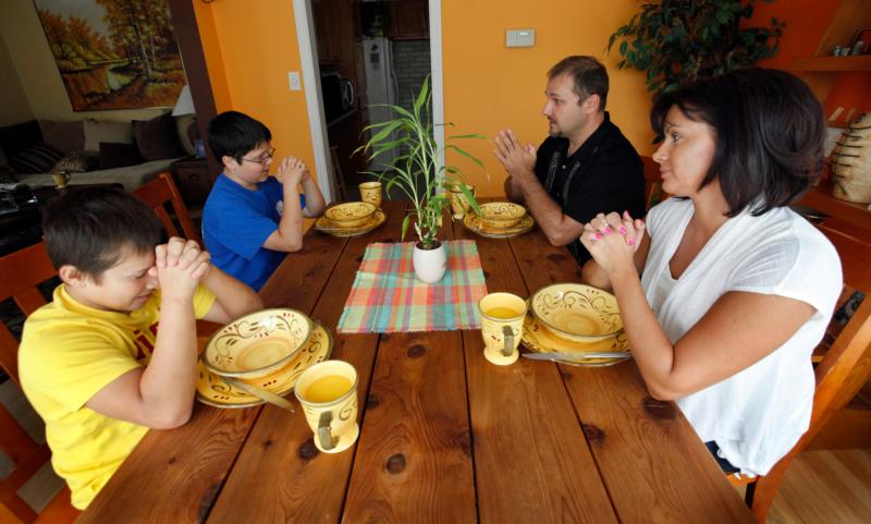 "A family prays together before a meal in 2012 at their Chicago home. A family that chooses to watch TV or play with their smartphones rather than talk at the dinner table is ""hardly a family,"" Pope Francis said. (CNS photo/Karen Callaway, Catholic New World)"