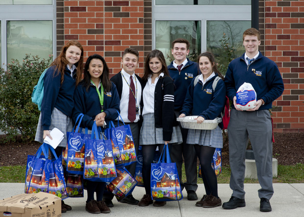 Students pause to show the result of their collection of donations for Thanksgiving meals, before heading out on the road to deliver the gifts.