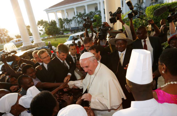 Pope Francis greets people as he arrives with Ugandan President Yoweri Museveni at the State House in Entebbe, Uganda, Nov. 27. (CNS photo/Paul Haring)