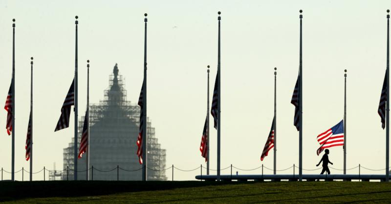 The dome of the U.S. Capitol is seen as a man walks past flags flying at half staff at the Washington Monument on the National Mall in Washington Nov. 16. (CNS photo/Kevin Lamarque, Reuters)
