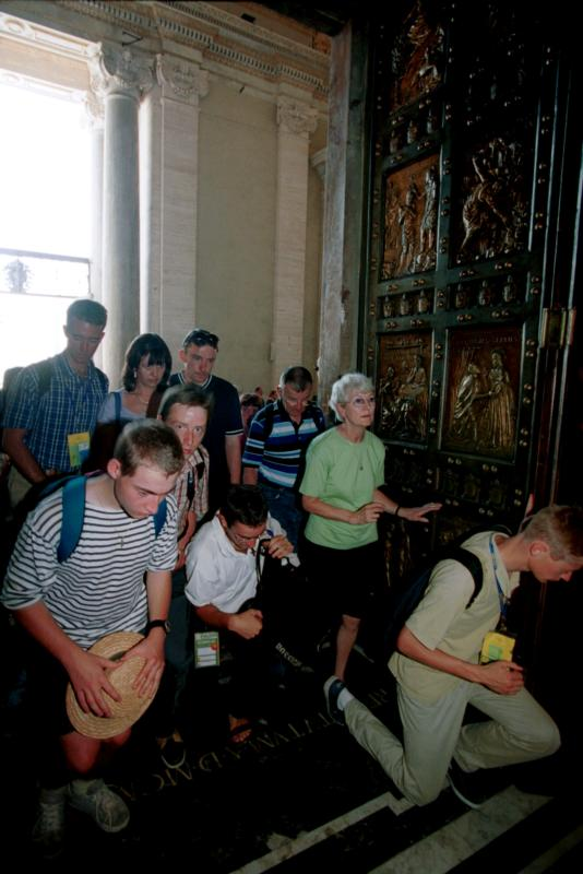 Pilgrims pass through the Holy Door in St. Peter's Basilica at the Vatican in this June 2000 file photo. Pope Francis will open the Holy Door in St. Peter's Dec. 8 during a Mass marking the opening of the Holy Year of Mercy. (CNS photo/Catholic Press Photo)
