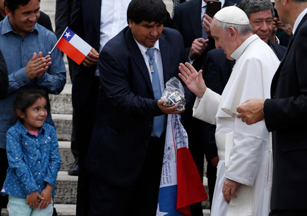 Pope Francis blesses religious objects as he meets Chilean miners during his general audience in St. Peter's Square at the Vatican Oct. 14. (CNS photo/Paul Haring)