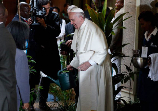 Pope Francis waters a tree he planted during a visit to the United Nations Office in Nairobi, Kenya, Nov. 26. (CNS photo/Paul Haring)