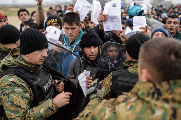 "Migrants and refugees show their ID papers to Macedonian police Nov. 20 and wait to cross the Greek-Macedonian border near Gevegelija, Macedonian. The extensive vetting process that all refugees undergo before arriving in the United States, ""screens out any possible threat of terrorism,"" said the executive director of the U.S. bishops' Migration and Refugee Services. (CNS photo/Georgi Licovski, EPA)"