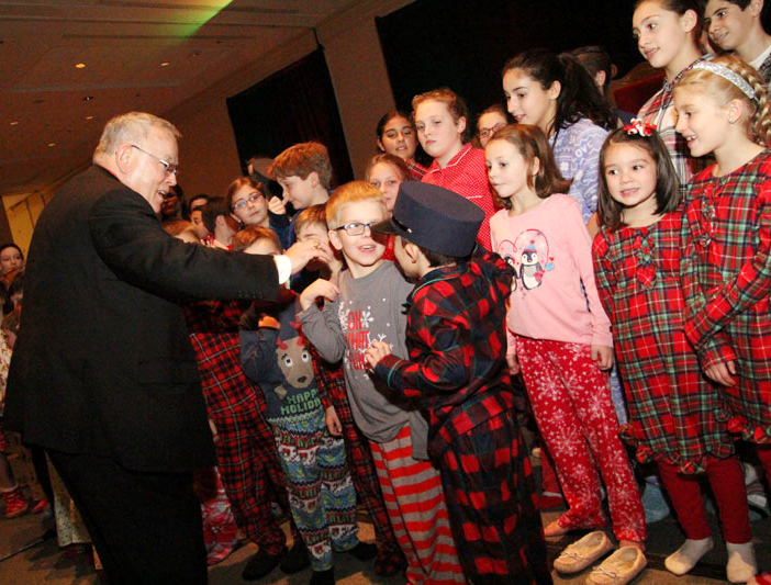 "Archbishop Charles Chaput puts a conductor's cap on a member of the Catholic Community Choir, the children's group that entertained attendees of the Archbishop's Christmas Benefit for Children Dec. 17 at the Sheraton Philadelphia Center City Hotel. The theme of the event was ""Polar Express."" (Photo by Sarah Webb)"