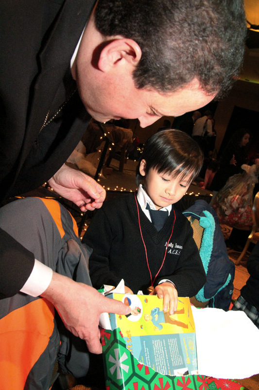 Bishop John McIntyre helps a young boy from Holy Innocents unwrap his presents delivered by Santa's helpers.