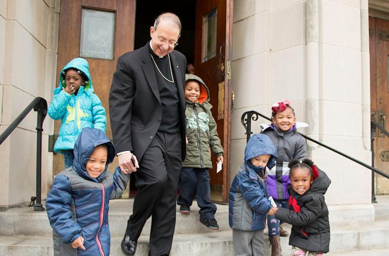 Archbishop William E. Lori of Baltimore walks with children from Catholic Charities Head Start Nov. 30 after helping distribute 1,000 winter coats donated by the Knights of Columbus to neighborhood children at St. Edward in Baltimore. (CNS photo/Olivia Obineme, Catholic Review)