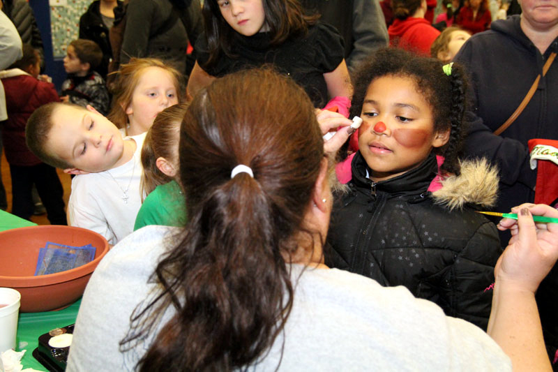 Kaitlynn Forbes gets her face painted to look like a reindeer.