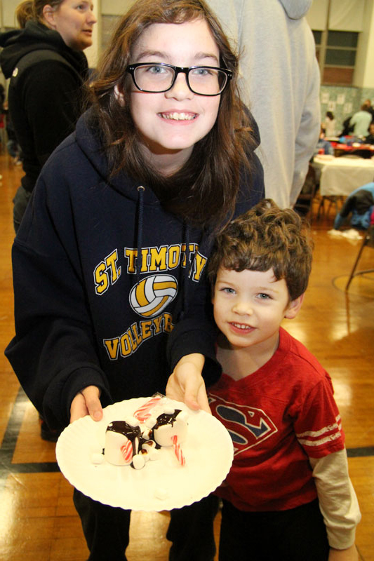 Siblings Norah and Kyran Fletcher are excited to eat the marshmellow snowman they made.