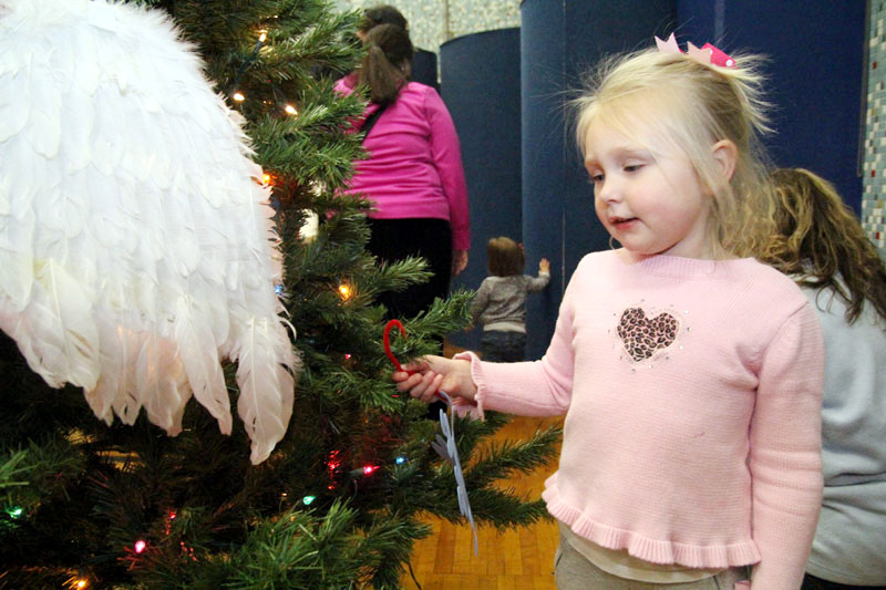 Maeve Fagan hangs the Christmas ornament she made on the tree.