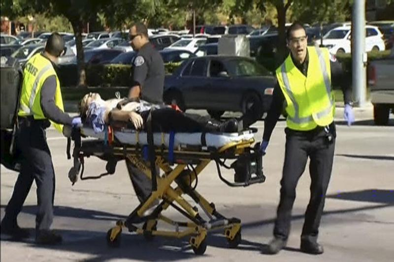 Rescue crews rush an injured victim to a waiting ambulance outside the Inland Regional Center in San Bernardino, Calif., in this still image taken from video Dec. 2. At least 14 people were reported killed and more than a dozen injured when gunmen opened fire that day during a function at a center for people with developmental disabilities, police said. (CNS photo/NBCLA.com/Handout via Reuters)
