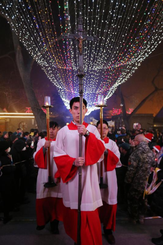 An altar server carries a crucifix as he leads a procession during Christmas Eve Mass at a Catholic church in Beijing.  (CNS photo/Wu Hong, EPA)