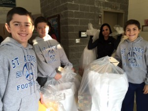 St. Agnes sixth graders Brendan McGrory and Colin McGrory, parent Allison Kealey, and sixth grader Joseph Sheridan helped bundle packages for distribution to local families