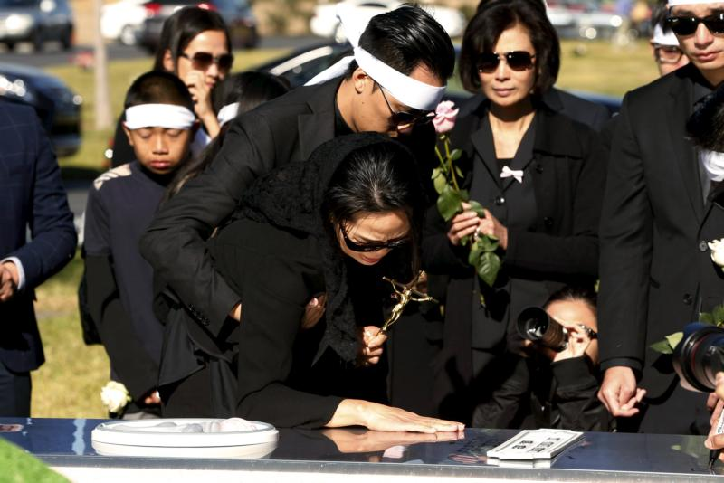 Van Thanh Nguyen touches the burial vault of her daughter, Tin Nguyen, during her Dec. 12 burial at Good Shepherd Cemetery in Huntington Beach, Calif. Nguyen was one of 14 victims killed in a Dec. 2 mass shooting at a social services center in San Bernardino. (CNS photo/Patrick T. Fallon, Reuters)