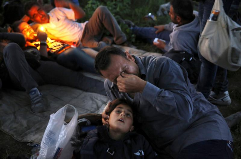 "A Syrian refugee cries next to his 7-year-old daughter after crossing the border into Macedonia in early May near the Greek village of Idomeni. A coalition of religious leaders joined three U.S. senators on Capitol Hill Dec. 8 to say ""enough is enough"" to those who want to bar Muslim refugees from Syria and other Middle East trouble spots. (CNS photo/Yannis Behrakis, Reuters)"