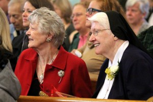 Betty Crosson, who first petitioned Bishop John O'Hara to start St Lucy School, and  Sr. Anne Marie Harrison, one of the first teachers and later principal, are all smiles as students perform a concert for guests.