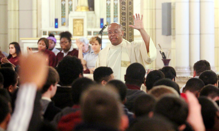 Father Stephen Thorne, pastor of Saint Martin De Porres Church, engages students during his homily.