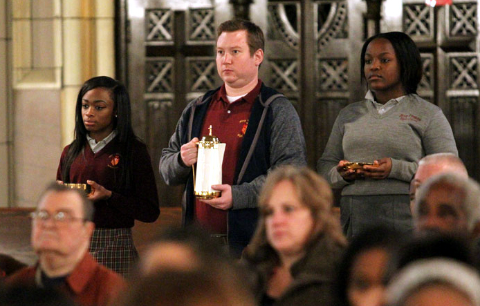 Tiara Robinson, English teacher Peter Ryan Tara Crews bring up the gifts during Mass which opens the Year of Mercy.
