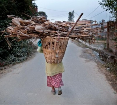 A Nepalese woman carries firewood on her back as she returns home in Lalitpur Dec. 21. (CNS photo/Narendra Shrestha, EPA)
