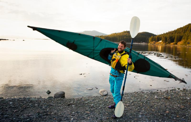 Outdoor enthusiast Father Thomas L. Weise stands with his kayak on a shoreline of Lynn Canal outside of Juneau, Alaska, in 2014. The 46-year-old priest of the Diocese of Juneau died Dec. 6 after suffering a cardiac arrest while visiting family in California. (CNS photo/Nancy Wiechec)