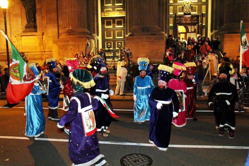 Members of Visitation Parish arrive as the chinelos dance in the street.