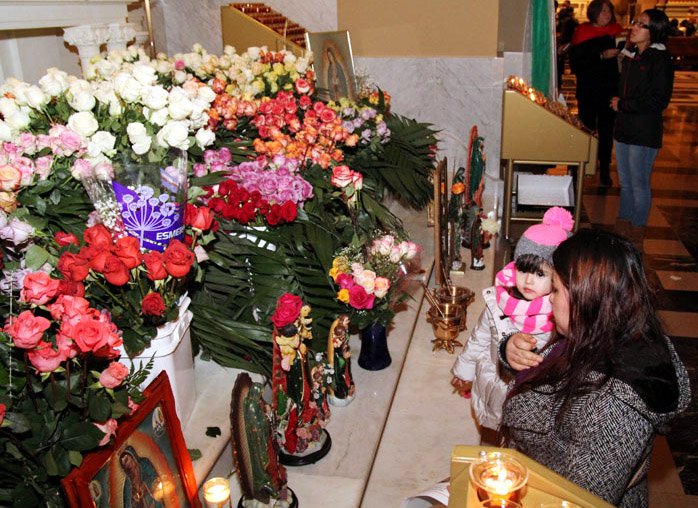Faithful place flowers before Our Lady of Guadalupe shrine and say a prayer.