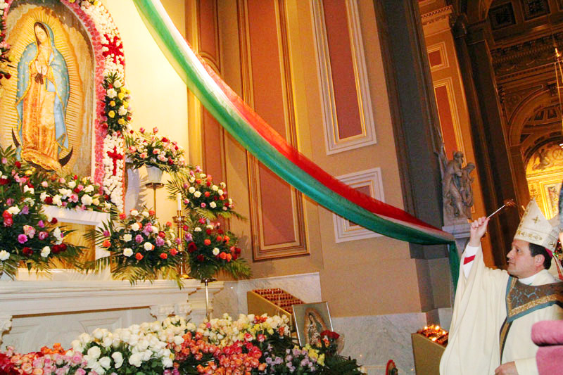 Bishop John McIntyre blesses the shrine of Our Lady of Guadalupe and the rose place before it by the people.