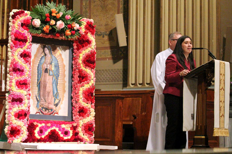 Kathia Arango. Director Office for Hispanic Catholics, welcomes people from all over the archdiocese before Mass.