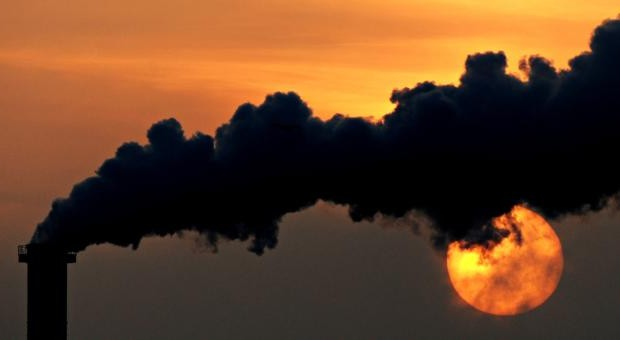 Smoke billows from a plant in late October at sunset in Wismar, Germany. (CNS photo/Daniel Reinhardt, EPA)