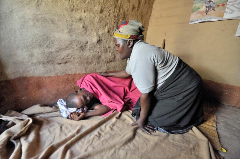 Home-based care worker Olipa Mkandawire prays for a man living with AIDS in Matuli, Malawi, in this 2009 photo. Marking World AIDS Day Dec. 1, African bishops commended families and parishioners caring for people with HIV as the Year of Mercy approaches. (CNS photo/Paul Jeffrey)