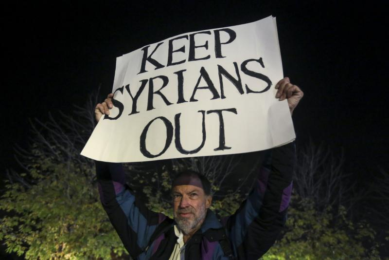 An anti-immigration protester holds up a sign as people take part in pro-immigration protest in the Manhattan borough of New York Dec. 10. Today's wave of anti-immigration rhetoric aimed especially at Syrian refugees echoes the anti-immigrant sentiments aimed at all manner of ethnic groups over the course of U.S. history. (CNS photo/Carlo Allegri, Reuters)