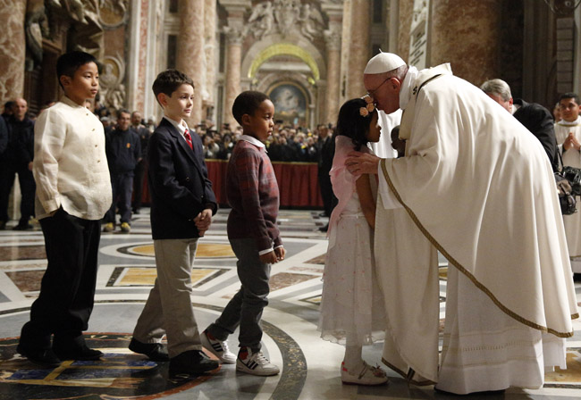 Pope Francis kisses children after celebrating Christmas Eve Mass in St. Peter's Basilica at the Vatican Dec. 24. (CNS photo/Paul Haring)