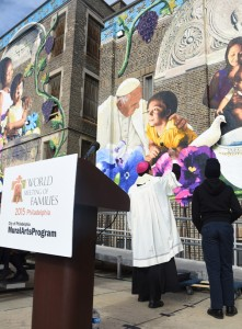 "Auxiliary Bishop John McIntyre blesses the 4,239 square foot outdoor mural, ""The  Sacred Now: Faith and Family in the 21st Century"" during a Nov. 30 dedication ceremony at St. Malachy School."