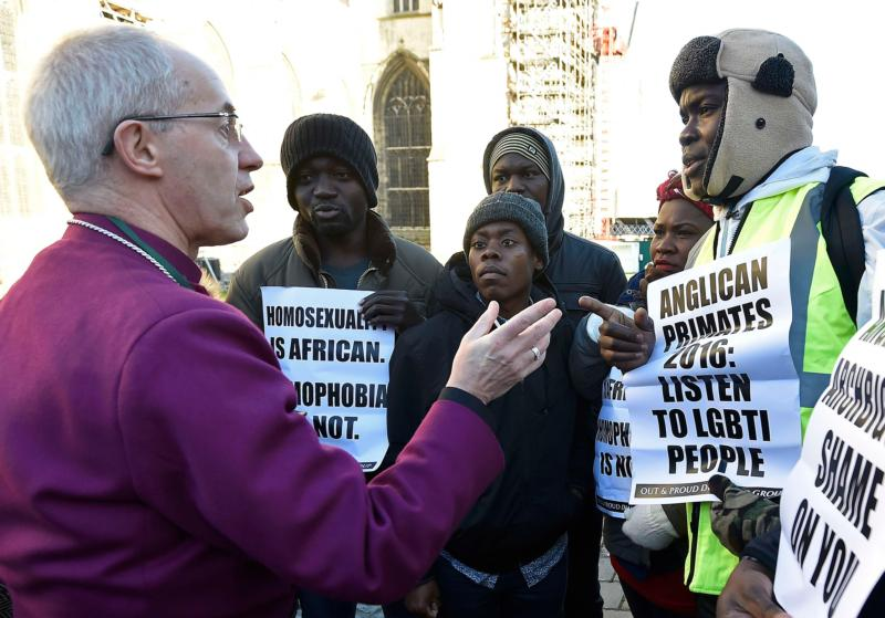 Anglican Archbishop Justin Welby of Canterbury, spiritual leader of the Anglican Communion, speaks with protestors on the grounds of England's Canterbury Cathedral, which was closed for a meeting of primates of the Anglican Church. At the meeting, Anglican leaders sanctioned Episcopalians over same-sex marriage. (CNS photo/Toby Melville, Reuters)