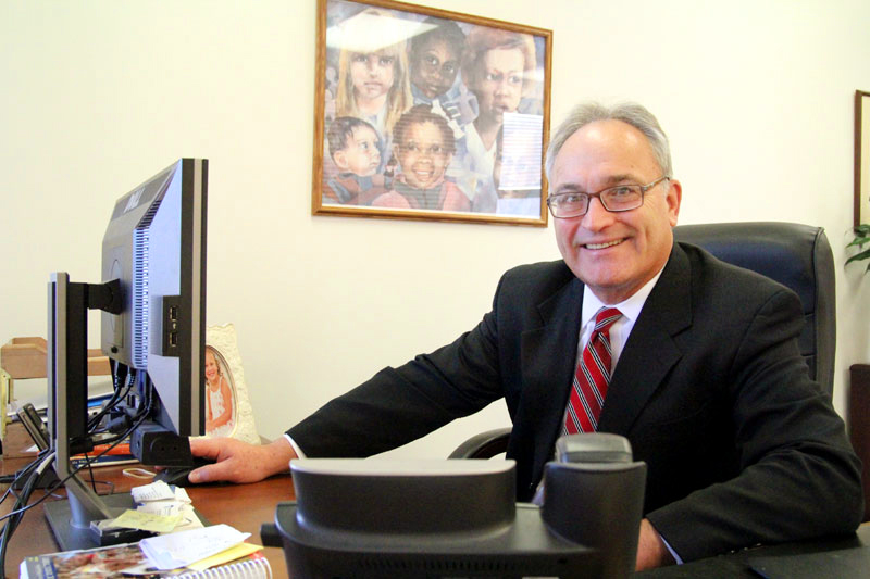 James Amato, secretary for Catholic Human Services for the Archdiocese of Philadelphia, works in his office in Philadelphia. (Photo by Sarah Webb)