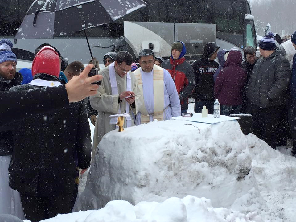 Father Patrick Behm of Le Mars, Iowa, checks out his cellphone during Mass Jan. 23 at an altar constructed of snow alongside the Pennsylvania Turnpike. The group from the Diocese of Sioux City, Iowa, was returning home from the annual March for Life rally in Washington when Winter Storm Jonas consumed the East Coast. Also pictured is Father Damien Wee of the Archdiocese of Omaha, Nebraska. (CNS photo/courtesy Carolyn Von Tersch)